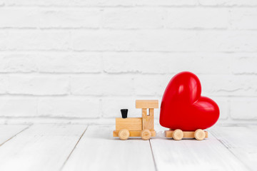 Red heart shaped on wood train over white background with copy space