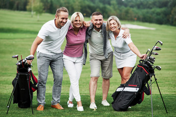 Beautiful woods at background. Photo of friends hugging and smiling with golf equipment after the game