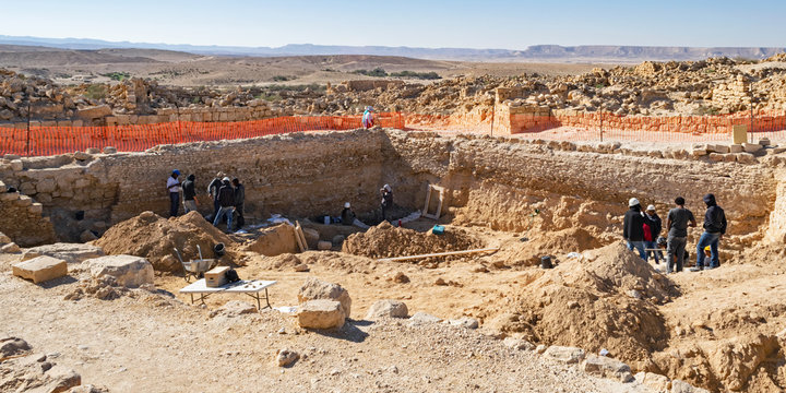 an archaeological dig at shivta national park in israel showing archaeologists and workers excavating the ruins of the water pools