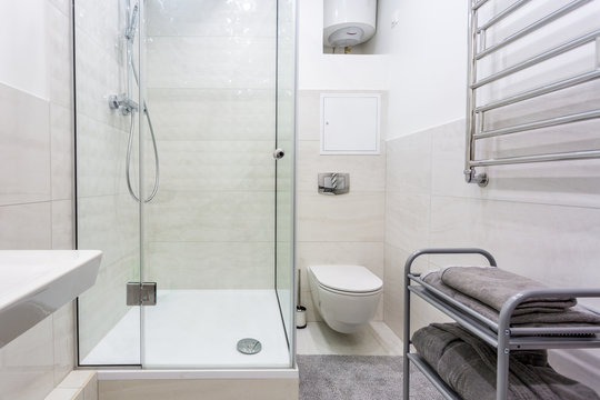 toilet and detail of a corner shower cabin with wall mount shower attachment