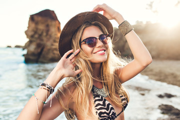 Portrait of attractive blonde girl with long hair posing on rocky beach. She wears bikini, hat, sunglasses. She is smiling. Wall mural