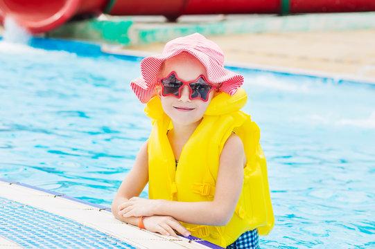 Sweet girl in the swimming pool wearing sunglasses