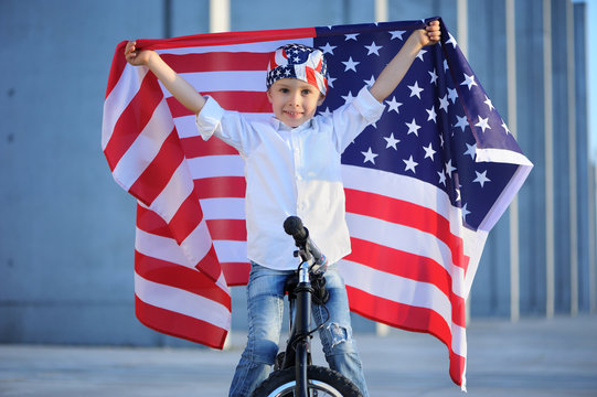 Happy handsome boy  smiling and waving American flag outside, wearing  Jackster Bandana. Child celebrating 4th july - Independence Day of USA.