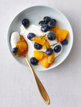 Blue Bowl of Yogurt with Blueberry Peach Topping