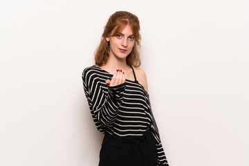 Young redhead woman over white wall inviting to come with hand. Happy that you came