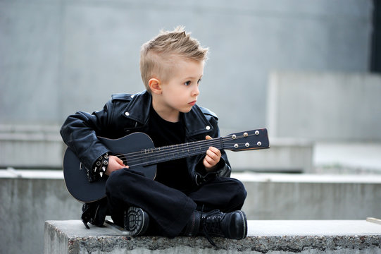 A handsome boy in black leather jacket, with  iroquois haircut, playing rock music on the guitar, sitting crossed legs. Rock and roll. Outdoor.