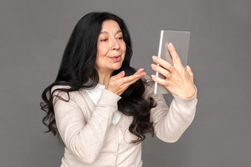 Freestyle. Mature lady standing isolated on grey sending kiss to camera having call on digital tablet close-up