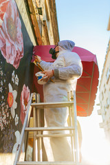 Young graffiti artist painting mural outdoors on street wall.