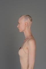 bald girl in beige lingerie posing on grey background