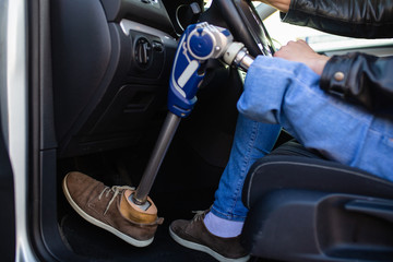 Young man with prosthetic leg driving car. Selective focus.