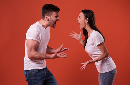 Side view photo of young angry and shouting couple in white t-shirts