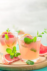 Fresh pink alcoholic cocktail with grapefruit, ice and mint