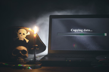 Illegal data copying concept. Cybercrime. Computer piracy background. Pirate hat, human skull, laptop and compact disc on a table.