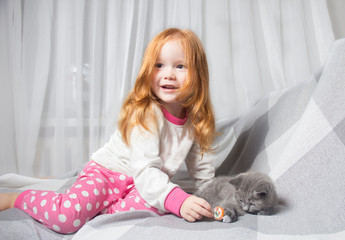 Little girl relaxing on the bed with her kitten. Child is kissing a cat