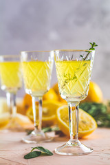 Liqueur limoncello with pieces of lemon and rosemary herb