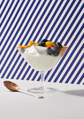 Yogurt in Glass with Mango and Blueberry topping with Striped Background and spoon