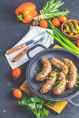 Fried sausage in a frying pan, with herbs and spices