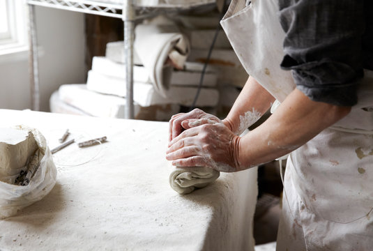Woman preparing clay for making ceramics in studio