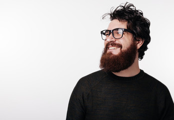 Attractive bearded man with stylish hair and beard smiling and looking away