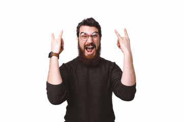 Excited bearded guy with crazy face expression is going rock symbol with hands up