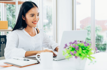 Young asian casual businesswoman using laptop computer working and communication with customer for order purchasing abd delivering information in modern home office, online shopping business concept