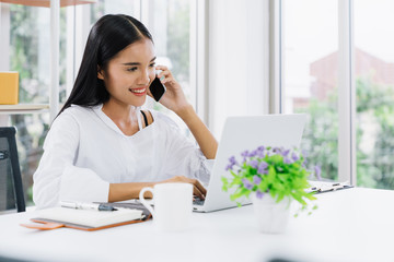 Young asian casual businesswoman using mobile phone and laptop to communicate with customer for order purchasing abd delivering information in modern home office, online shopping business concept