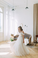 Fees in the interior Studio in the European style. The bride in a white wedding dress.