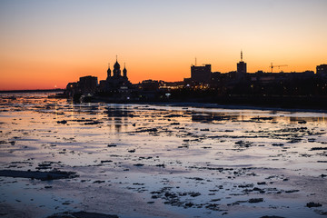 Ice drift in Northern Dvina river in Arkhangelsk, Russia. Beautiful ice motion evening silhouette citiscape.