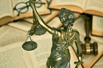 Statue of justice, judge gavel and open books.