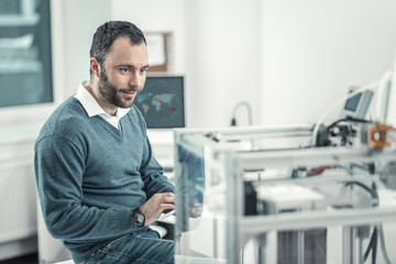 Delighted smart man sitting near the 3d printer