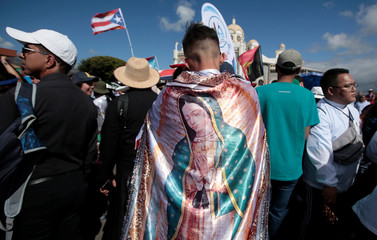 A pilgrim wears a silk shawl with the image of the Virgin of Guadalupe as he takes part in a religious ceremony at Basilica de Los Angeles before leaving for Panama to participates in the third World Youth Day with Pope Francis, in Cartago