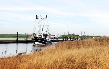 Krabbenkutter auf dem Weg zum Krabbenfang in in der Nordsee, idyllischer Kutterhafen an der Nordseeküste in Wremen bei Bremerhaven