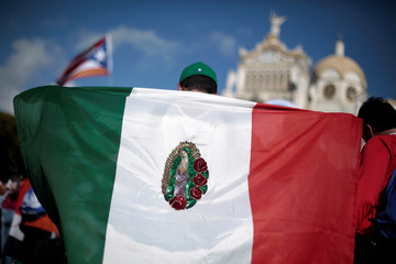 A pilgrim wears a Mexican flag with the image of the Virgin of Guadalupe during a religious ceremony at Basilica de Los Angeles