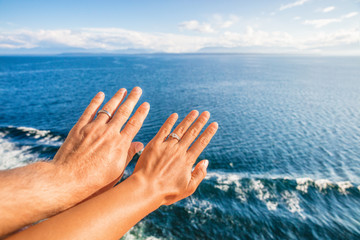 Cruise honeymoon travel vacation for newlyweds couple showing wedding rings on hand selfie at ocean view resort background. Luxury holidays.