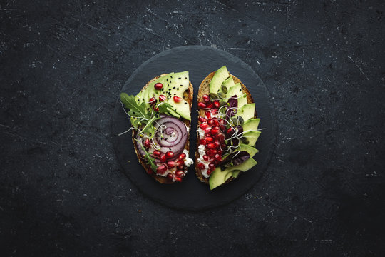Healthy food. Avocado toasts with avocado slices, seeds and sprouts on dark background.