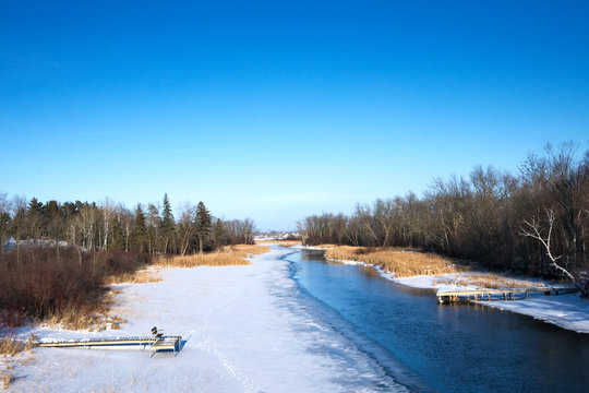 Mississippi River flows north toward Bemidji Minnesota near hiway 2 on a sunny day. This winter scene includes boat docks in snow and ice.
