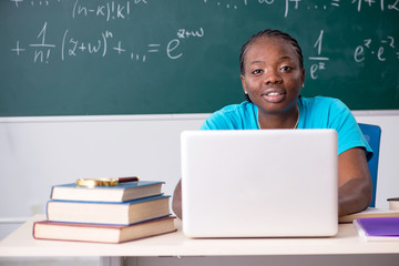 Black female student in front of chalkboard