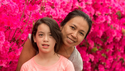 Mother and Daughter standing in front of pink azalea flowers in tshirt on hot spring day