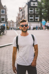 A man with a backpack walks through the streets of Amsterdam.