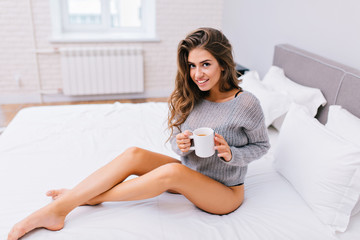 Good morning of happy pretty girl with long brunette hair chilling in modern apartment. Joyful young woman with naked long legs, in knitted grey sweater with a cup of tea on white bed