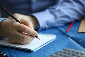 Male hand hold black pencil on blueprint