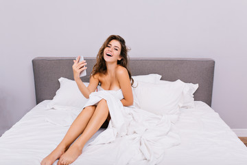 Joyful smiling naked girl with long hair chilling in white bed in the morning in modern apartment. True positive emotions, enjoying relaxation, having fun, beautiful model, pleasure