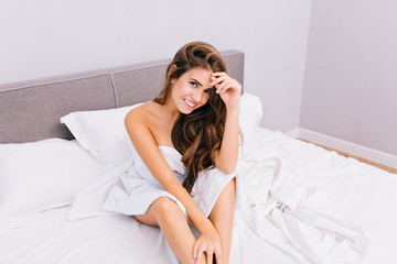Attractive young woman chilling in bed in modern apartment. Joyful amazing smiling girl with long brunette hair relaxing at home. Waking up, positive true emotions, good morning, cute lovely model