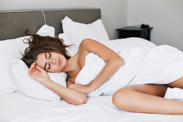 Attractive young girl sleeping on white bed in modern apartment in the morning