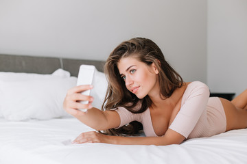 Portrait attractive young girl in pajama laying on bed in apartment. She takes a selfie portrait on phone