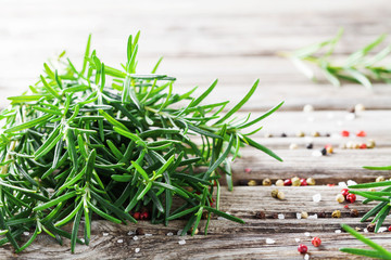 Fresh aromatic rosemary for cooking on wooden table.