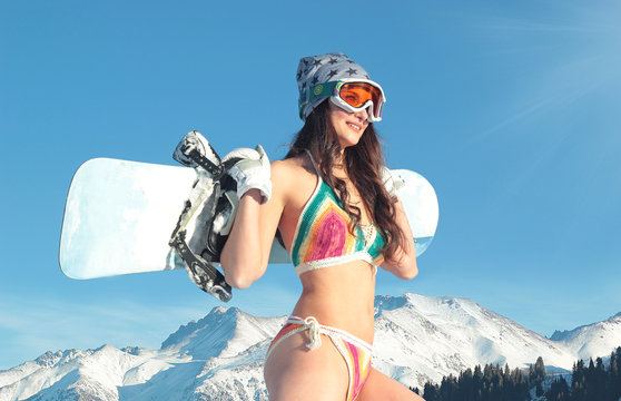 Smiling bikini girl holding snowboard on her shoulders