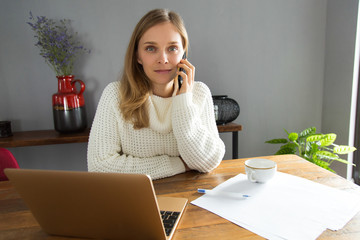 Freelance call center operator working at home. Content young woman talking on mobile phone and looking at camera. Home office concept