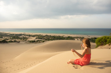 Girl in red relaxing in sandy desert