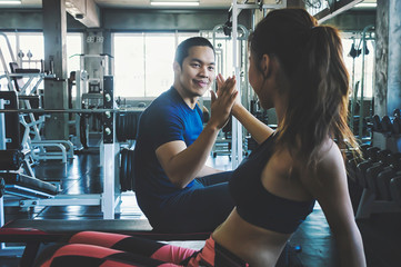Fitness man and woman giving each other a high five after the training session in gym. Fit couple high five after workout.